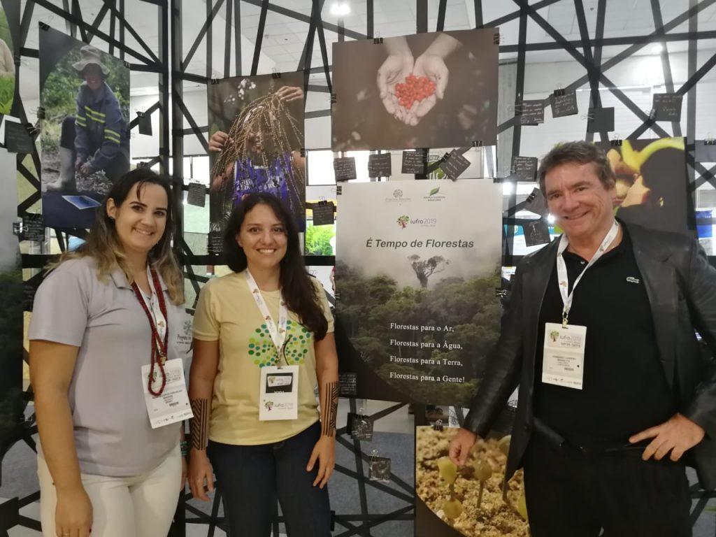 Frente al stand del proyecto Arboretum, el cual está a cargo del Bosque Modelo Hileia Baiana, Natalia y Renata del Bosque Modelo Hileia Baiana, y Fernando Carrera, gerente de la Secretaría de la Red Latinoamericana de Bosques Modelo.